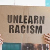 """The phrase """" Unlearn racism """" on a banner in men's hand with blurred background. Stop discrimination. Inequality. Pressure. Tension. Unlawful. Human rights. Illegal. Conflict"""